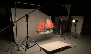 photo studio set up with lights and grey seamless background. model boat artifact hovering in the foreground